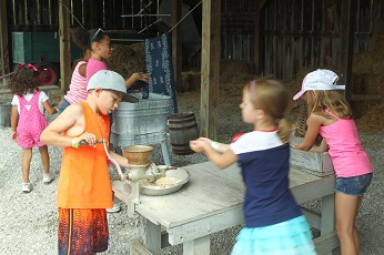 kids have fun grinding corn